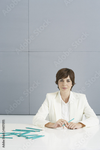 Businesswoman with large number of blue pencils