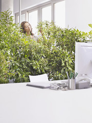 Businesswoman tending overgrown plants in office