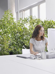 Businesswoman at desk surrounded by plants
