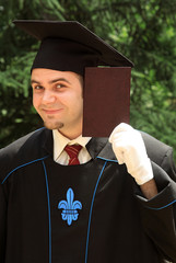 Male graduate holding diploma proudly outdoor