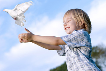 Little boy releasing a white pigeon in the sky.