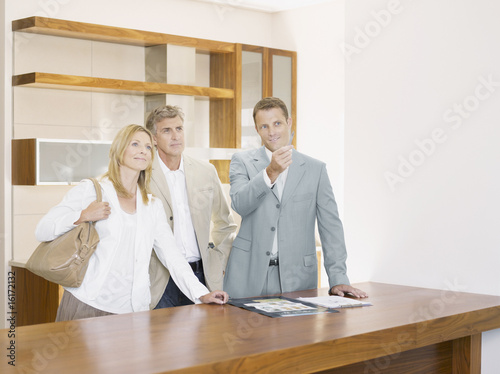 Salesman with couple in interior design showroom