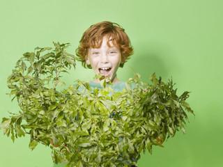 Young hiding behind green bush