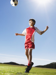 Young boy in uniform heading soccer ball