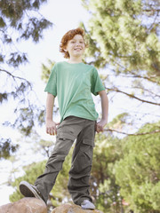 Young boy standing on rocks in park