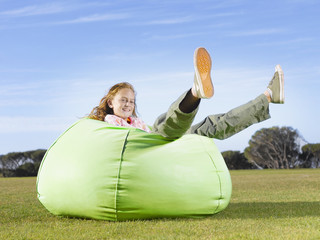 Young girl relaxing in bean bag outdoors