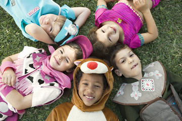 Children in costume laying in the grass