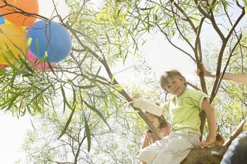 Children sitting in tree at birthday party