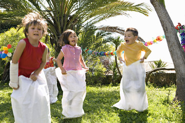 Children running sack race at birthday party