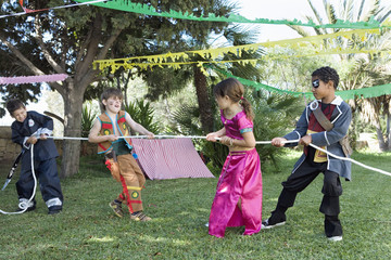 Children in costume playing tug-of-war