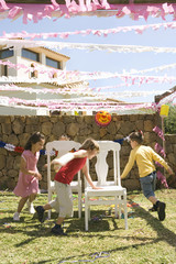 Children playing musical chairs at birthday party