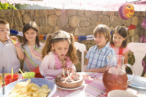 Girl blowing out candles at birthday party