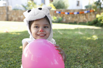 Young girl in rabbit costume with balloon