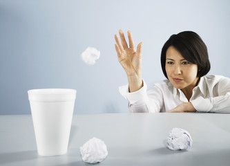 Businesswoman throwing wastepaper into styrofoam cup