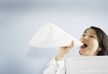 Businesswoman shouting through paper megaphone