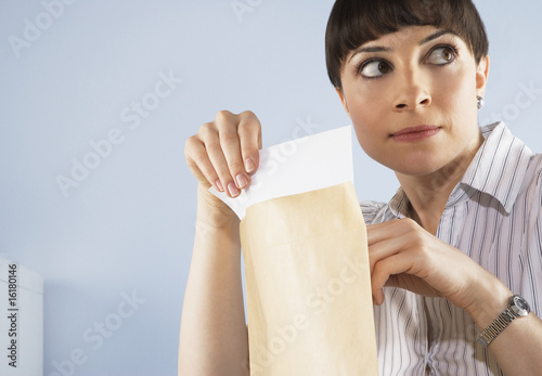 Businesswoman peaking at confidential documents