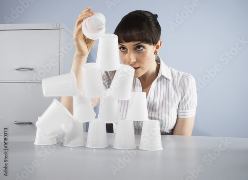 Businesswoman stacking plastic cups into pyramid