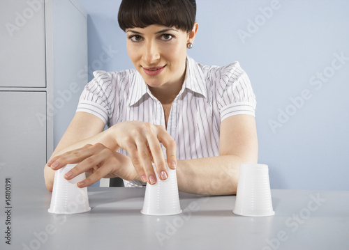 Businesswoman playing hide and seek game with cups