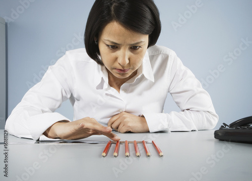 Businesswoman carefully counting pencils