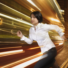Businesswoman running with lights streaking behind