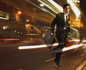 Businessman running with light streaking around him
