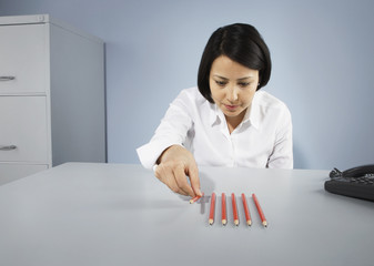 Businesswoman carefully lining up pencils
