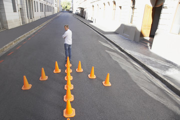 Man standing with arrow-shaped traffic cones in roadway