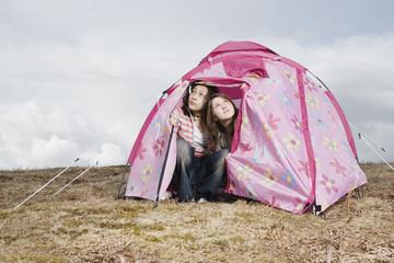 Teenage girls camping in pink tent