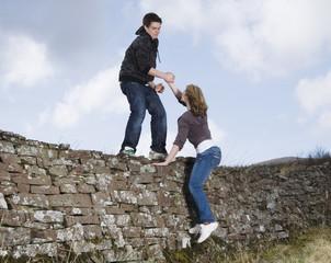Teenage boy helping girlfriend over rock wall