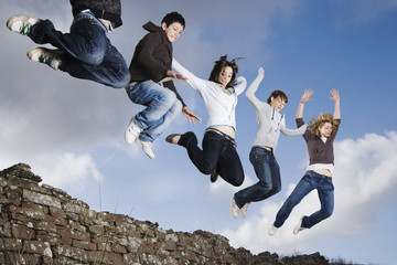 Teenage friends jumping off rock wall