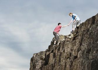 Teenage boys rock climbing