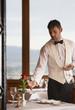 Waiter arranging glasses in elegant restaurant