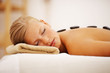 Stone massage therapy: Cute woman relaxing at a spa