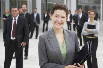 Businesspeople posing in office building courtyard