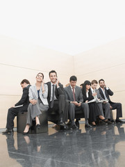 Businesspeople sitting on crowded bench