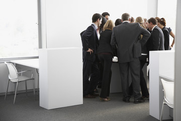 Businesspeople gathering in corner of office