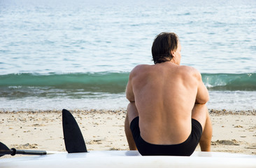 A mature surfer sitting alone on beach.