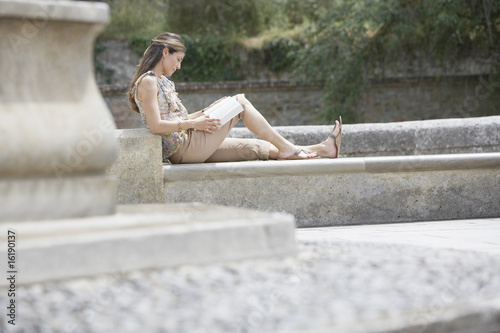 Woman reading book on stone steps