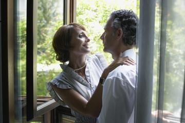 Romantic couple hugging near window