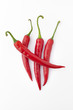 Four red hot peppers on white background