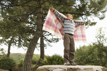 Boy standing on rock with arms outstretched