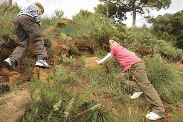 Children climbing rocky hill