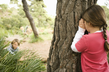 Children playing hide and seek in forest