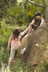 Boy helping girl up rock