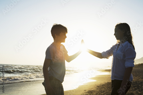 Friends touching hands on beach