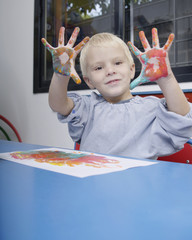 Boy finger-painting in classroom