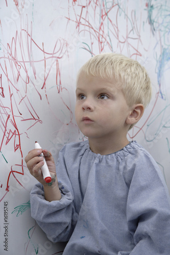 Boy scribbling on whiteboard