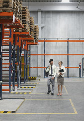 Businesspeople walking in warehouse