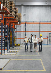 Businesspeople and workers in warehouse