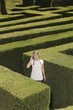 Young woman lost in hedge maze